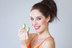 Girl With Cucumber Slices. Happy fresh girl with cucumber slices over studio background Stock Images