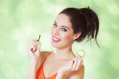 Girl With Cucumber Slices. Happy girl with cucumber slices over green sparkling shiny background Stock Photos