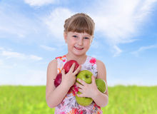 Girl cuddle a lot of big apples. Stock Image