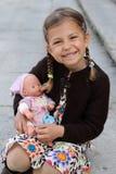 Girl cuddling doll Stock Photos