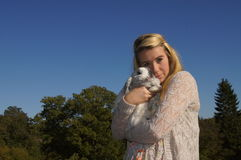 Girl Cuddling her Rabbit. Girl cuddling her grey lop-eared rabbit Royalty Free Stock Image