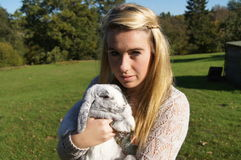 Girl Cuddling her rabbit. Girl cuddling her grey lop-eared rabbit Royalty Free Stock Photography