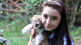 Girl cuddling a puppy outdoors stock footage