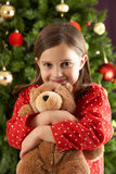 Girl Cuddling Teddy In Front Of Christmas Tree Royalty Free Stock Photo