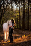 Girl Cuddling White Horse in Woods. A beautiful young woman with dark long hair is seen cuddling a handsome white horse in a wood with tall trees and golden stock photography