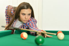 Girl with cue playing billiard Stock Photo