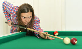 Girl with cue playing billiard Stock Photos
