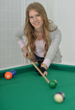 Girl with cue playing billiard Stock Photography