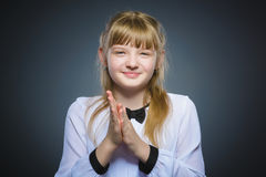 Girl cunning, studio photo isolated on a gray background.  Royalty Free Stock Photos