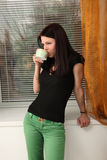 Girl with a cup. Beautiful girl in green trousers, black blouses drinking tea near the window Royalty Free Stock Photos