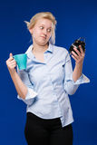Girl with cup and alarm clock in hands. Sleeping girl with a cup and alarm clock in hands on a blue background Royalty Free Stock Image