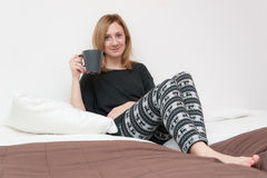 Girl With Cup in Bed Stock Images