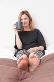 Girl With Cup in Bed Royalty Free Stock Photos