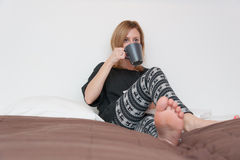 Girl With Cup in Bed Royalty Free Stock Image