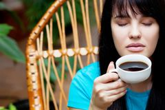 Girl with cup of coffee in garden Royalty Free Stock Images