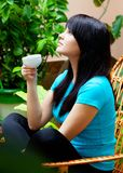 Girl with cup of coffee in garden Stock Photos