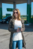 Girl with a cup of coffee at a gas station Stock Photography