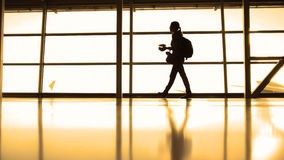The girl with cup of coffee going in airport in front window opposite the runway, silhouette, warm Stock Photo