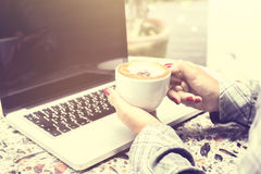 Girl with cup of coffee and laptop Royalty Free Stock Photography