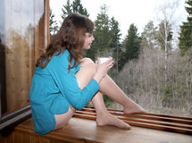The girl with cup of coffee looks at forest Royalty Free Stock Images