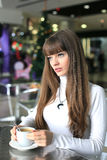 Girl with a cup of coffee in a shopping center Stock Images