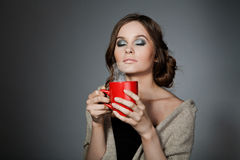 Girl with a cup in his hand, breathes fragrance. On gray background Royalty Free Stock Photo