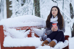 Girl with cup of hot drink at winter park Stock Photography