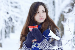 Girl  with cup of hot drink in winter park Stock Images