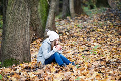 A girl with a  cup of hot tea blowing on it. A girl is sitting under the tree in the autumn park with a cup of hot tea in her hands .  She is blowing to make it Royalty Free Stock Images