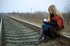 The girl with a cup sits on rails Stock Image