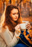 Girl with cup tea on a background of autumn forest Royalty Free Stock Photography