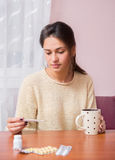Girl with a cup of tea checks temperature Royalty Free Stock Photo