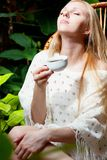 Girl with cup of tea in garden Royalty Free Stock Images