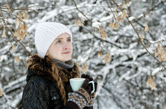 Girl with a cup of tea outdoors among the trees.  Royalty Free Stock Images