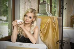 Girl with cup of tea in vintage cafe Royalty Free Stock Photo