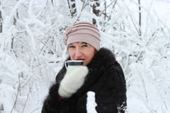 Girl with a cup of tea in the winter forest. Woman holding a cup of tea in the winter forest Royalty Free Stock Photography