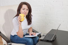 Girl with cup of tea works Royalty Free Stock Photography