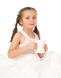 Girl with cup in white bed Royalty Free Stock Photo