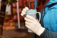 A girl and cup. The girl in white gloves is holding a cup of coffee in the winter , autumn season Stock Images
