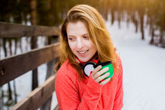 The girl with Cup in winter Park. Young beautiful girl with a Cup from the thermos in winter Park in the evening Stock Images
