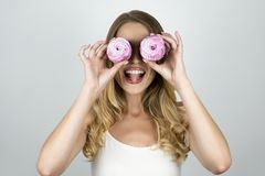 Girl with cupcakes near eyes looks happy isolated white background royalty free stock photography