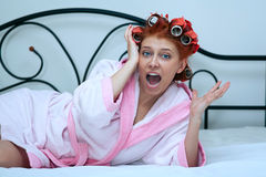 Girl in curlers on the bed Royalty Free Stock Photo