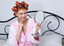 Girl in curlers on the bed Royalty Free Stock Photography