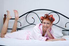 Girl in curlers on the bed Royalty Free Stock Images