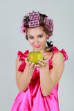 Girl in curlers and a green apple in hand. Apple in focus Stock Photos