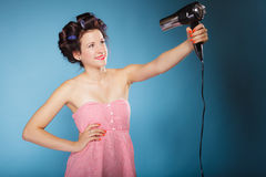 Girl with curlers in hair holds hairdreyer Royalty Free Stock Photo