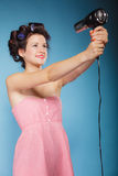 Girl with curlers in hair holds hairdreyer Royalty Free Stock Images