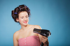 Girl with curlers in hair holds hairdreyer Royalty Free Stock Photography