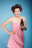 Girl with curlers in hair holds hairdreyer Royalty Free Stock Photos