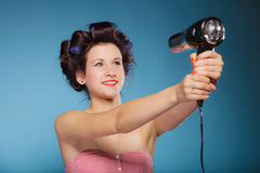 Girl with curlers in hair holds hairdreyer Stock Photos